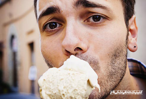 getty rf photo of man eating icecream cone - 15 مشکل رایج دندان