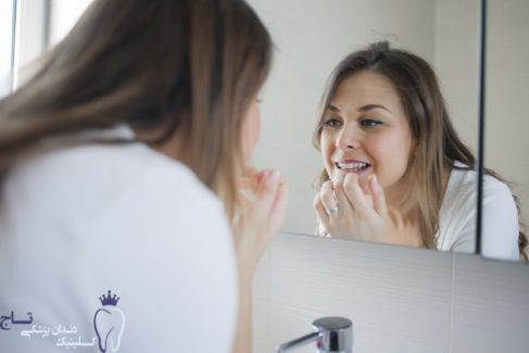 adult woman with loose tooth looking in bathroom mirror new e1551554427328 - چگونگی درمان دندان لق در بزرگسالان